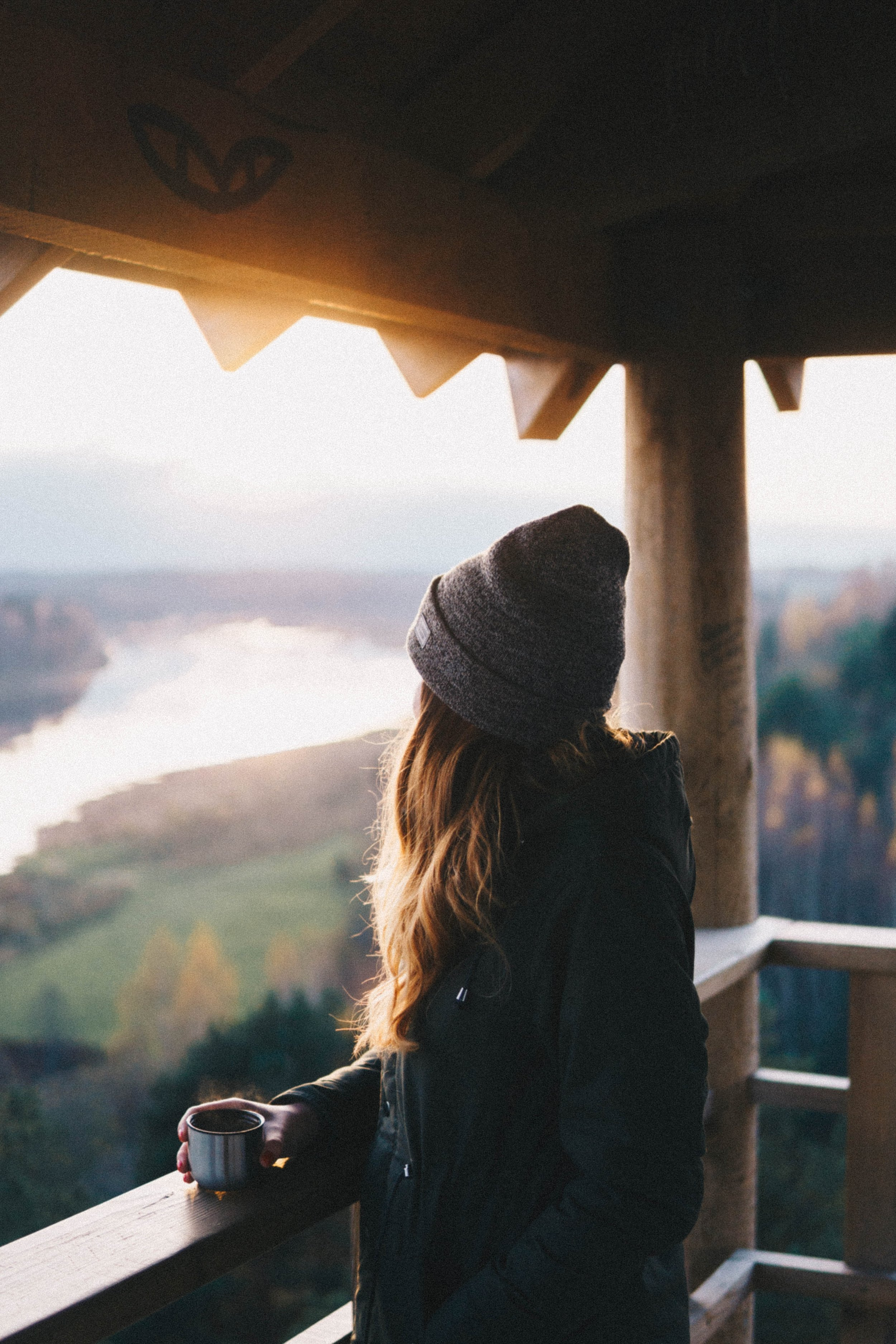 A woman with a mug standing at a railing, gazing out at a mountain valley