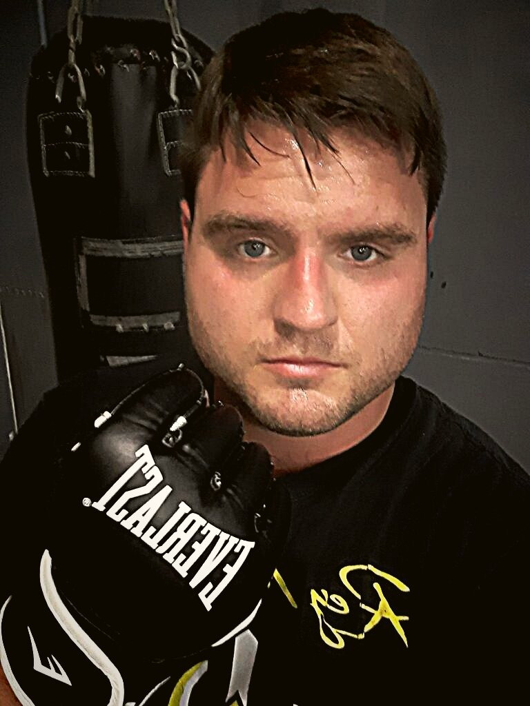 Justin Gillespie wearing boxing gloves, standing in front of a heavy bag