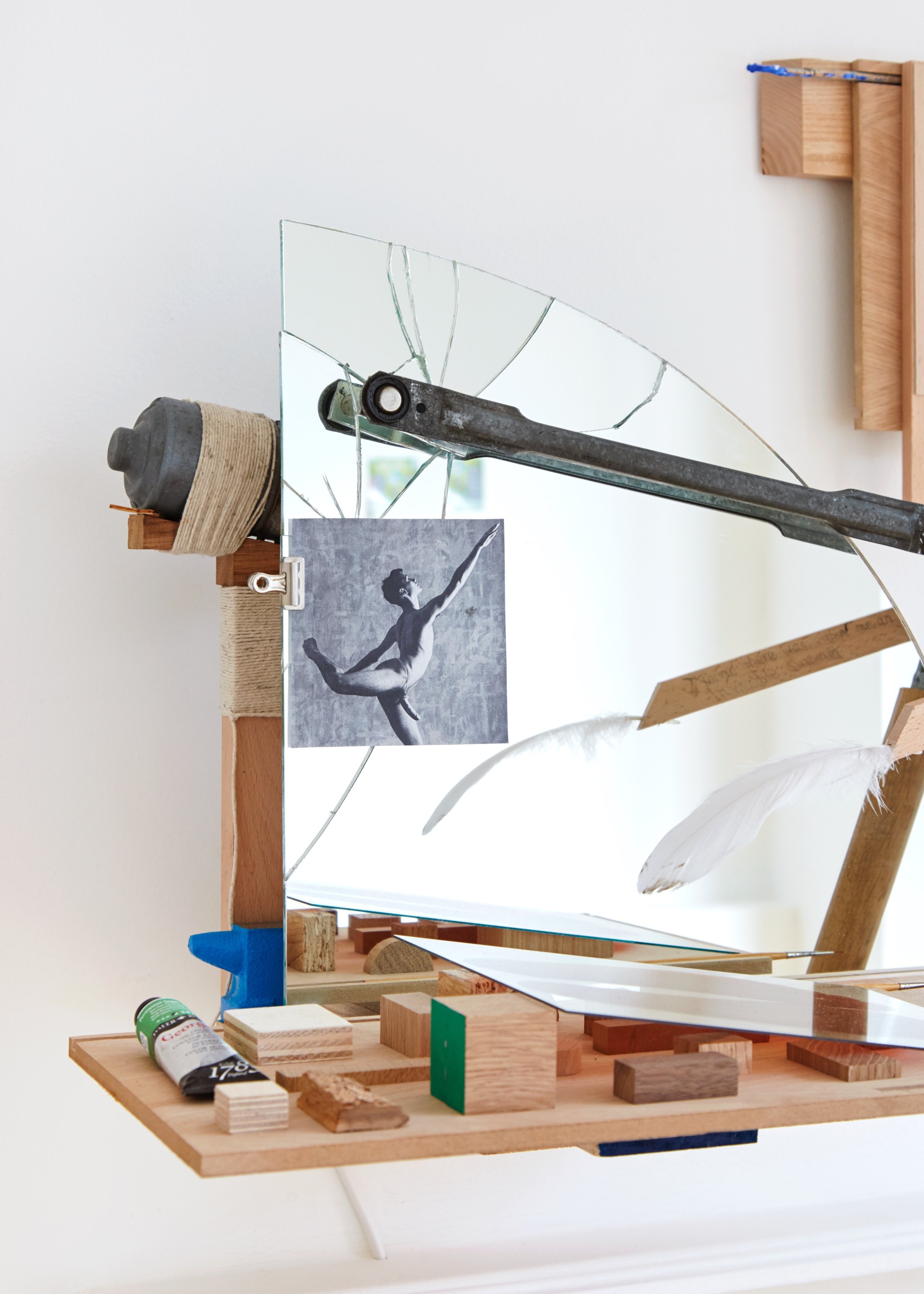 """Detail of  I found there was, within me, an invincible summer,  2019 Oak Veneered MDF, Pencil on Beech, Painted Oak, Glass, Assorted Pebbles from Cornwall and Lancaster, Pebble from Plymouth, Laser cut Plywood, Paint Brushes, Painted Anvil, Found Photograph of the Ballerina Michael Clark, Bulldog Clip, String, Wiper Motor and Mechanism, Arduino and Electronic Components, Broken Mirror, Pasted Torn Notes, Feather, Printed Sticker, Assorted Wooden Shapes (Chip Board, Plywood, Oak, Bark, Walnut, Douglas Fir, """"Permeant Green"""" Oil Paint in Tube and Various Fixings 58 x 95 x 45 cm"""