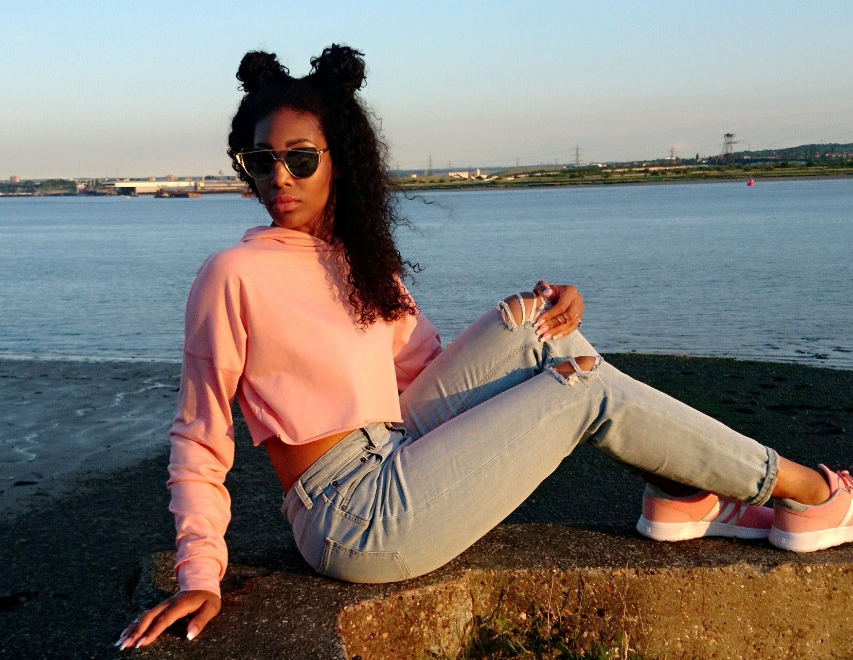 Curly hair, coral hoody light blue jeans and coral trainers