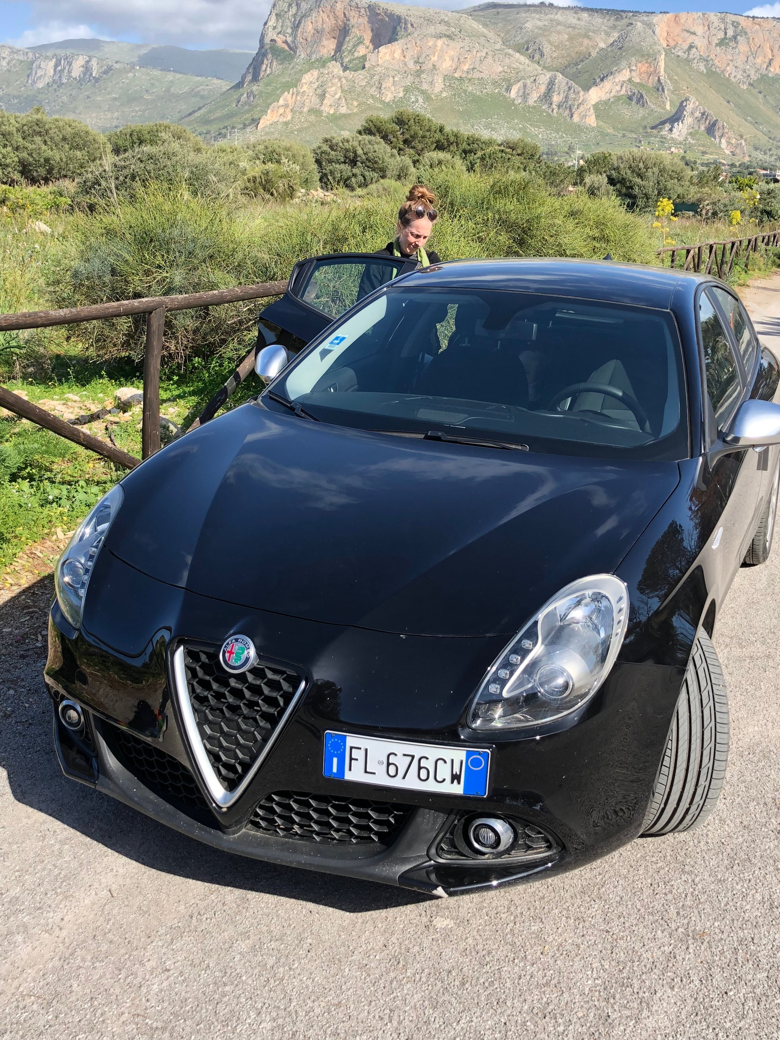 My wife posing with our Alfa Romeo. Most likely right after a gelato stop.