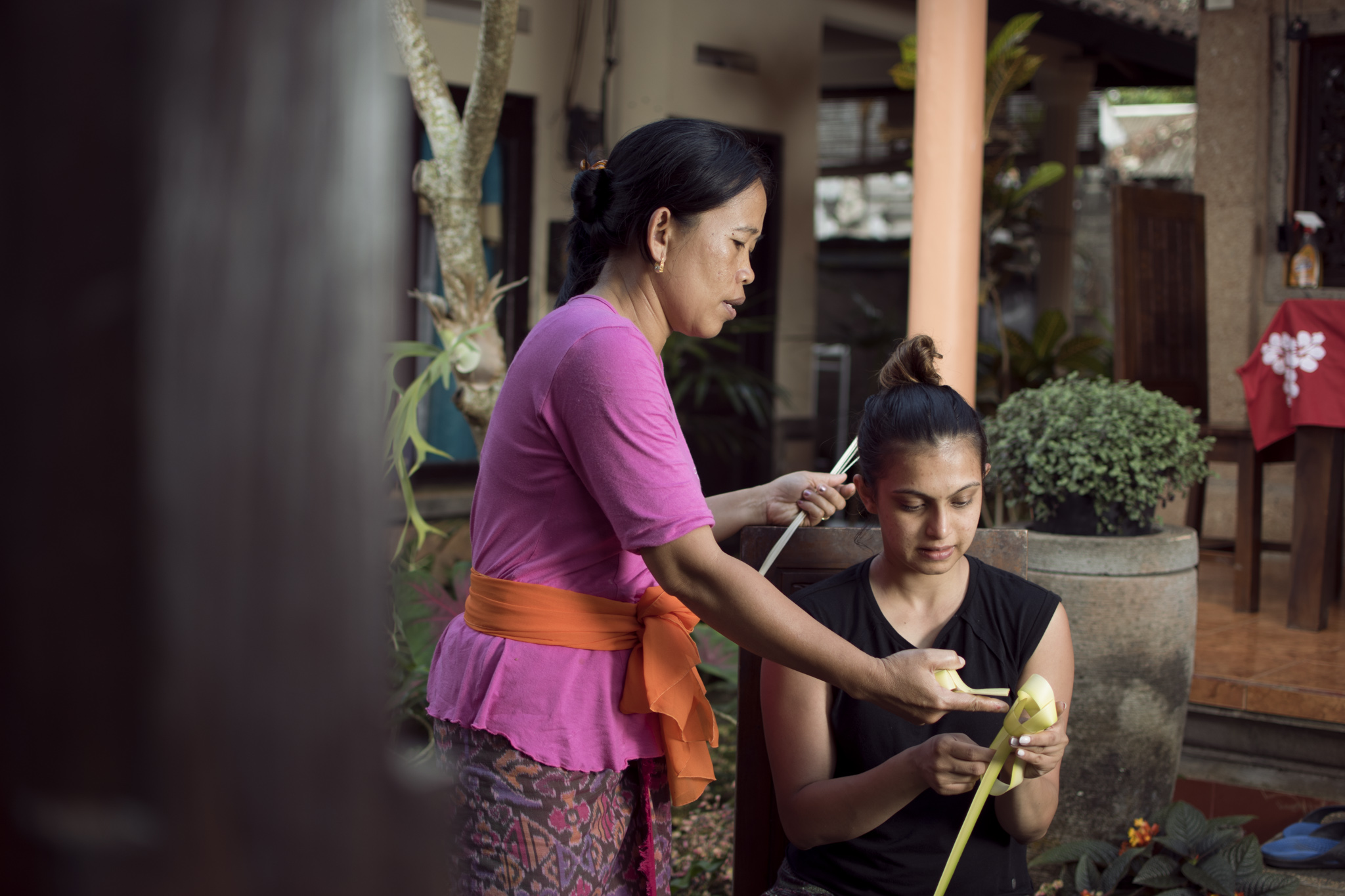 Nyoman, the wife of our host, showing us how to prepare 'Canang Sari' a daily offering that Balinese Hindus use to praise and worship the Gods.