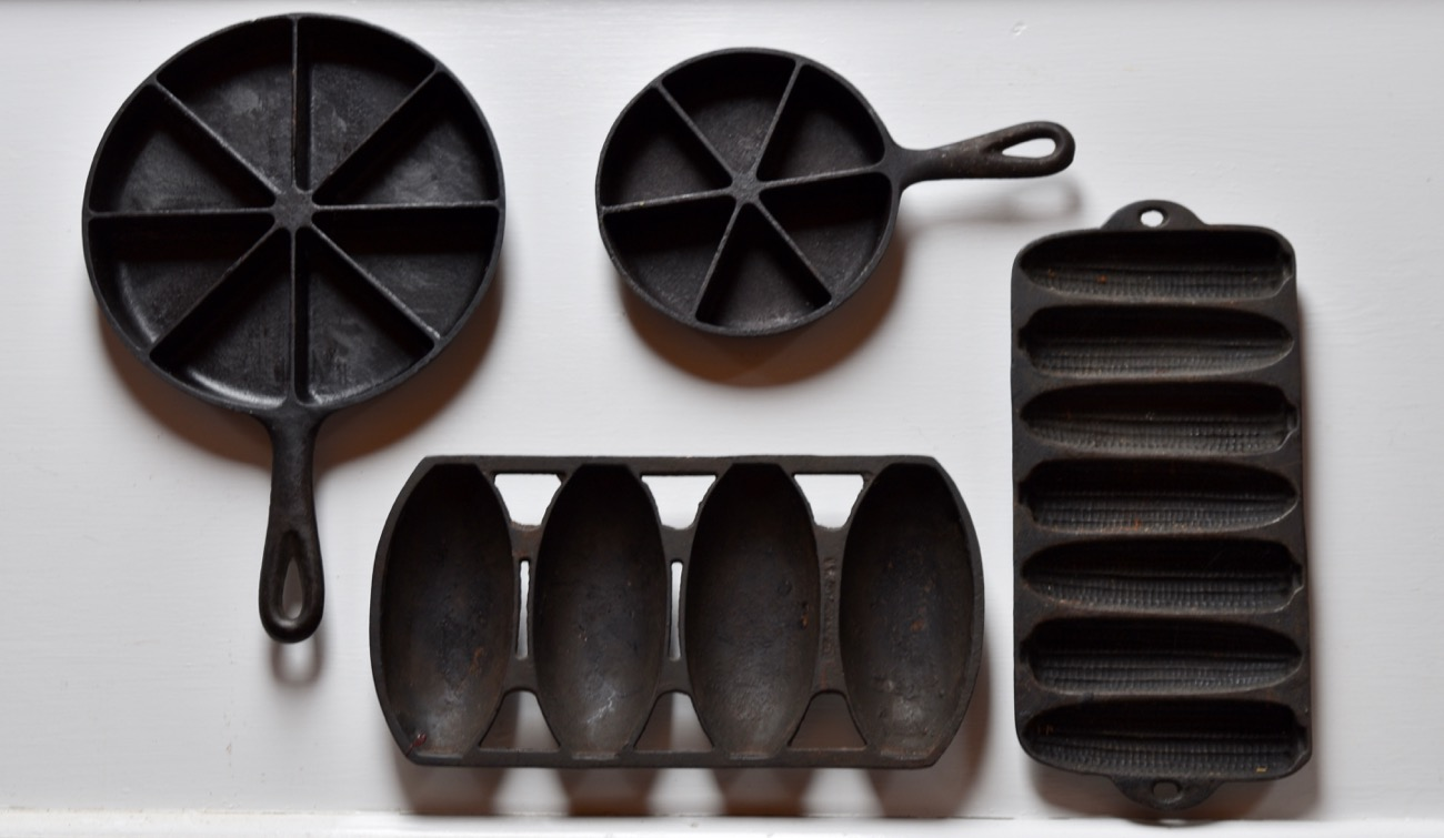 "Clockwise from far right: a cornstick pan, a rare sandwich roll pan, a typical 8"" cornbread skillet, and one of my favorite finds, a 5"" mini cornbread wedge pan."