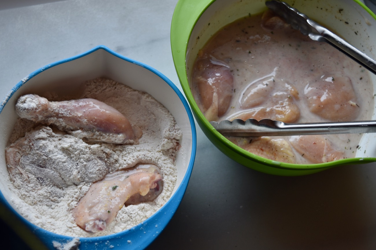 Pick up the soaking chicken pieces with tongs, let them drain, and put them in the flour mixture. Toss them around to coat on all sides.