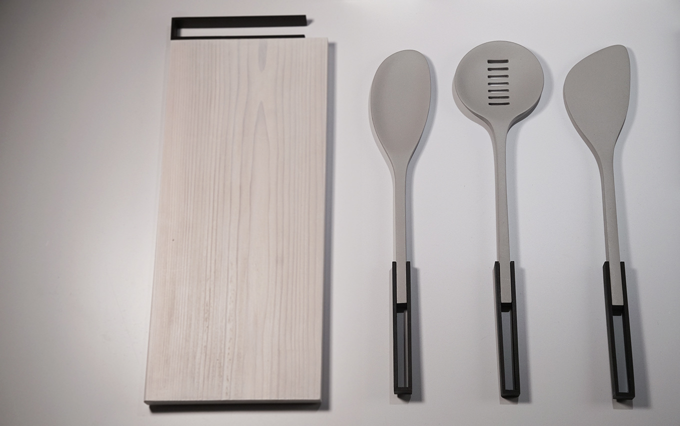 The cooking utensils include a spoon, slotted spoon, and a spatula. The organic nylon forms are attached to a metal frame handle.