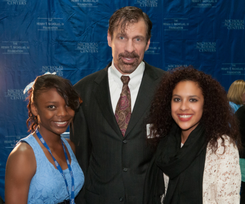 """Henry T. Nicholas, III, Ph.D., joins Nicholas Academic Center (NAC) students Erin Davis (left) and Jennifer Nava at the 4th Annual Thanksgiving Dinner Celebration. The Broadcom Co-Founder and former CEO told the more than 300 students and their families: """"One hundred percent of our students go on to college, and we're going to ensure that every one of them earns a degree."""" (Photo: Business Wire)"""
