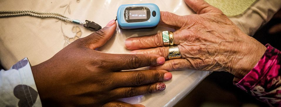 A nurse practitioner uses a pulse oximeter on a client at her home in Plainfield, N.J., Oct. 26, 2016. The Labor Department continues to police wage and hour violations by home care businesses.