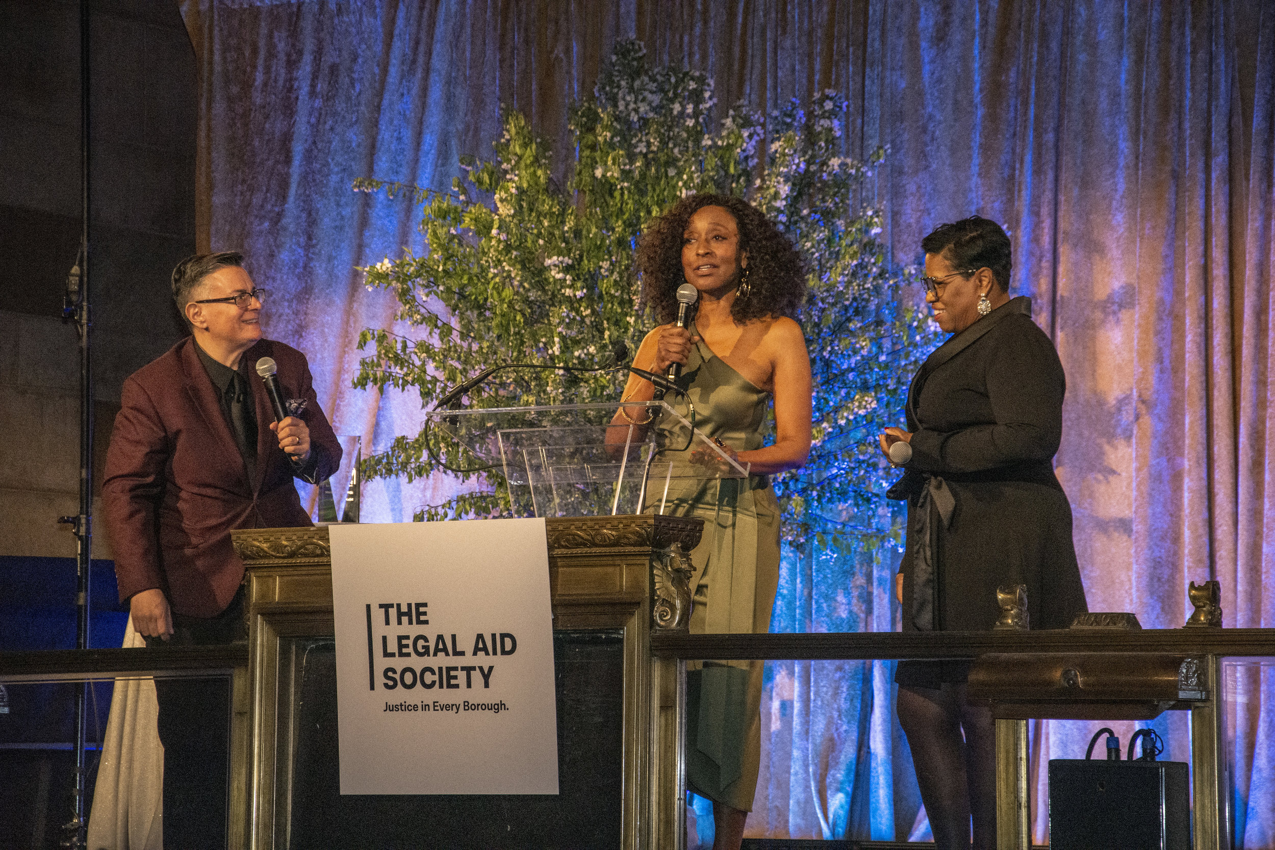 L-R: Tina Luongo, Adriene Holder, and Dawne Mitchell, Attorney's in Charge of the Criminal Defense, Civil, and Juvenile Rights Practices, engage the 700+ attendees during the Live Auction.