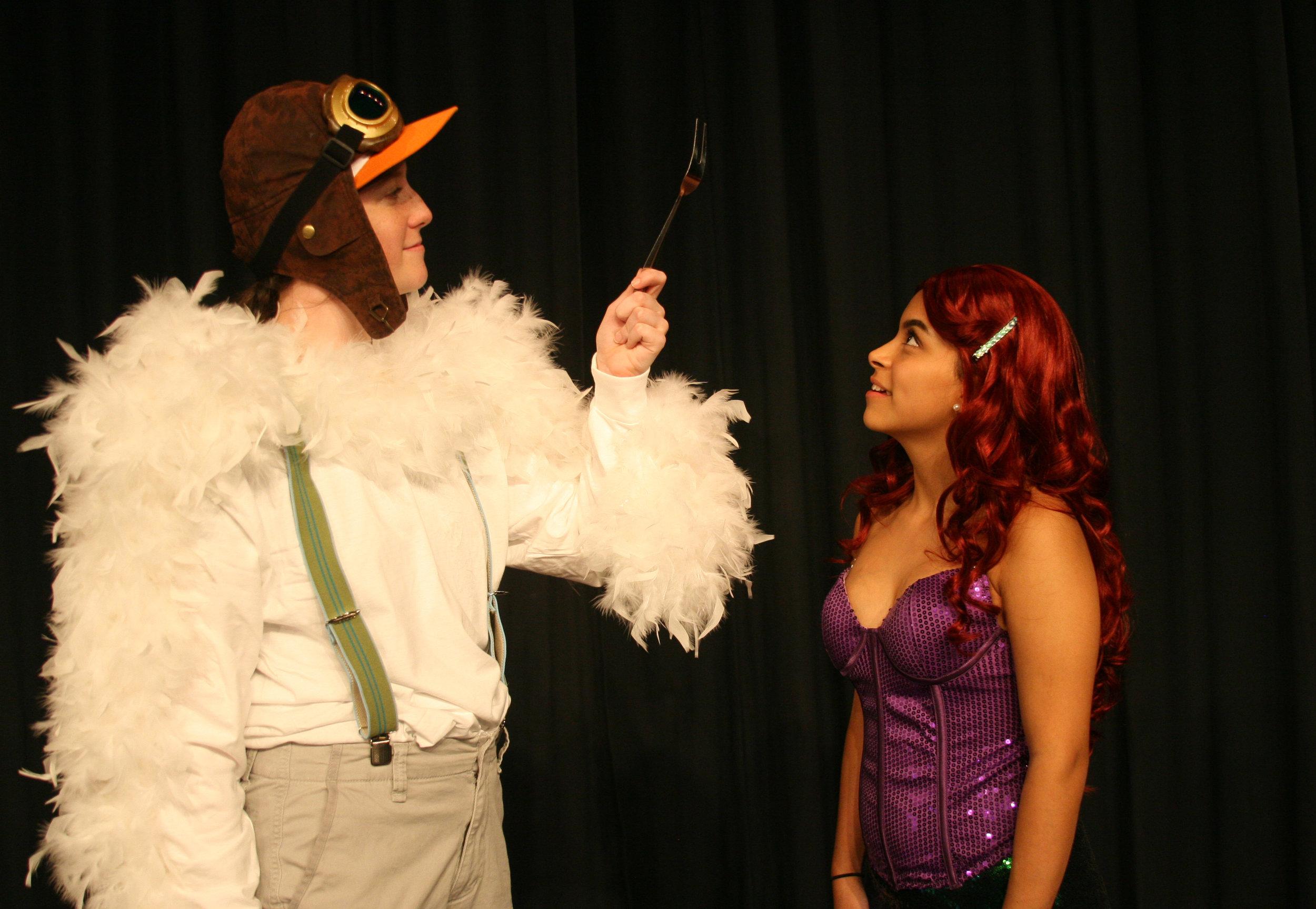 Scuttle the seagull (Jennifer Henderson) proudly displays his latest human artifact to Ariel (Jennifer Trejo Benitez).