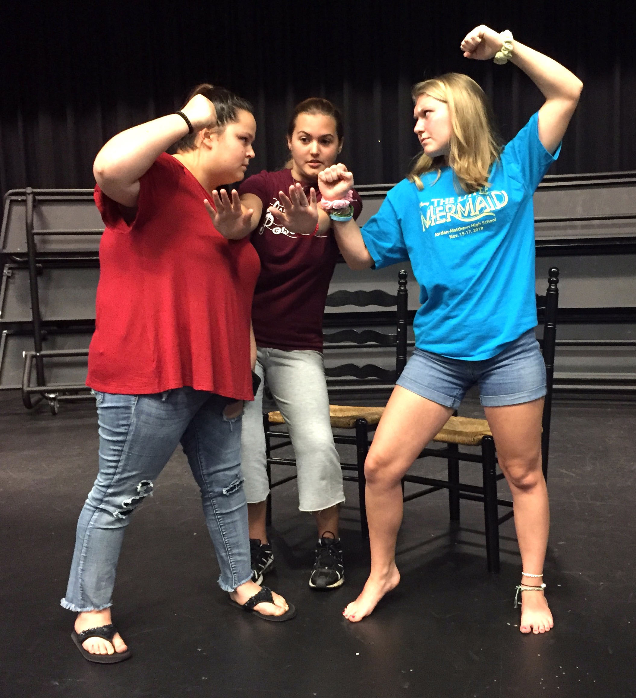 "Laci Burt, from left, Natalie Santiago and Hannah Redding ""freeze"" during their devised fight scene. Students will create similar improvised scenes as part of the free Scene X Scene performance showcase on May 2 at Jordan-Matthews High School."