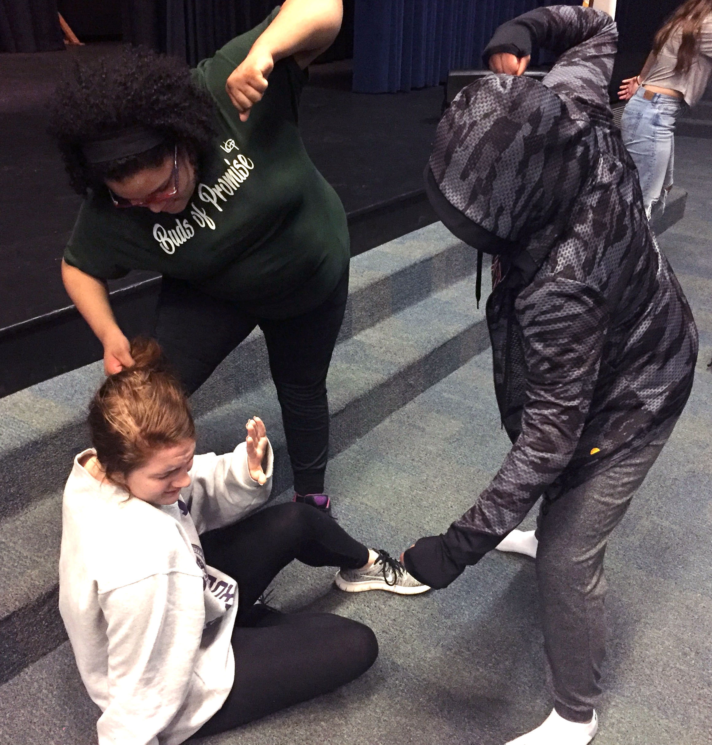 Zy'kiuh Marsh, left, and Gisselle Aleman Moreno threaten Corrine Collison as part of a small-group exercise during the Scene X Scene acting intensive at Jordan-Matthews.