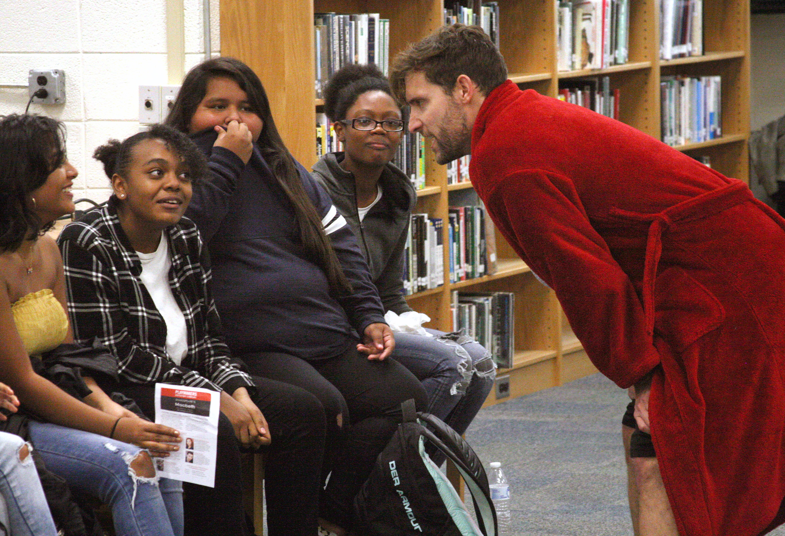 """Actor Adam Poole, right, interacts with audience members during last fall's performance of """"Macbeth"""" in the Jordan-Matthews High School Media Center. PlayMakers Repertory Company returns on October 17 for a free performance of """"Wilder & Wilder."""" (Photo by Chip Pate)"""