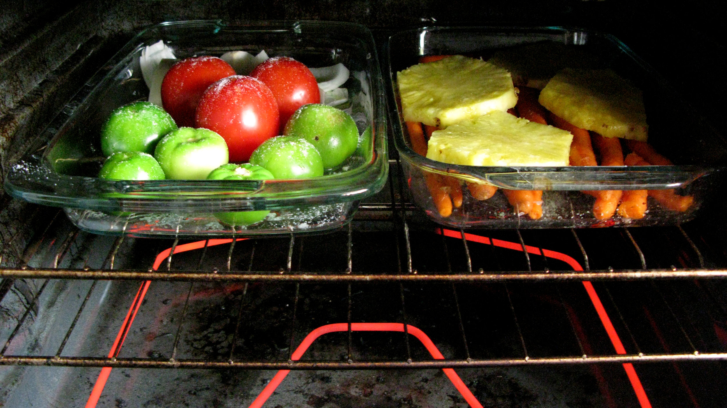 Tomatillos, tomatoes, onions, garlic, EVOO + salt on left; pineapples sitting on carrots on right; roasted at high temps until caramelized + sizzling.
