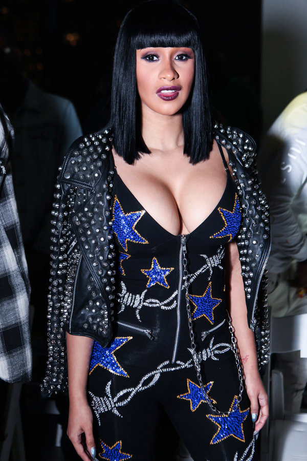 (via: Essence) Keeping it edgy, Cardi B rocks fitted black dress with a spiked leather jacket