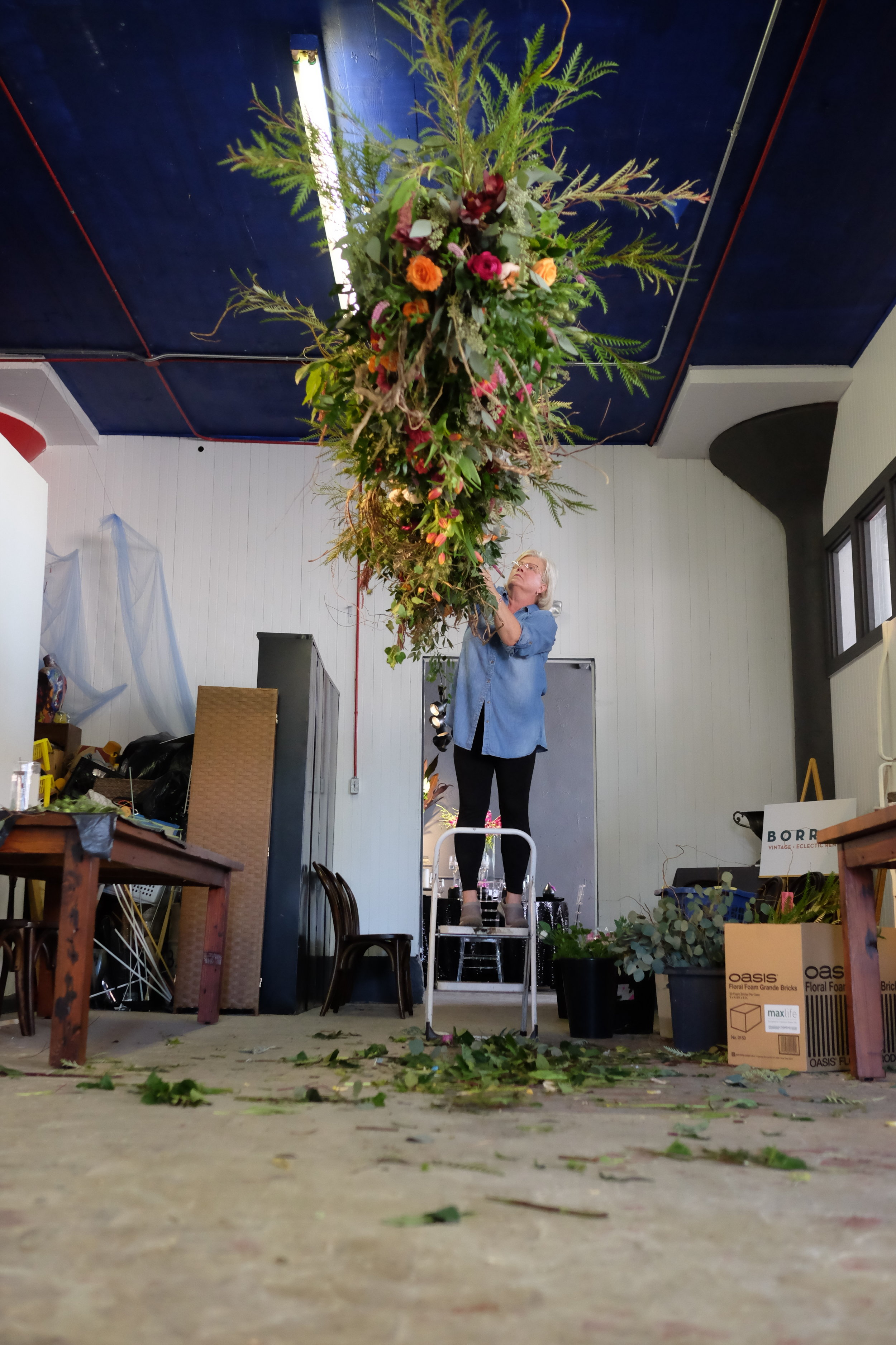 Sally making a hanging center piece of flowers.