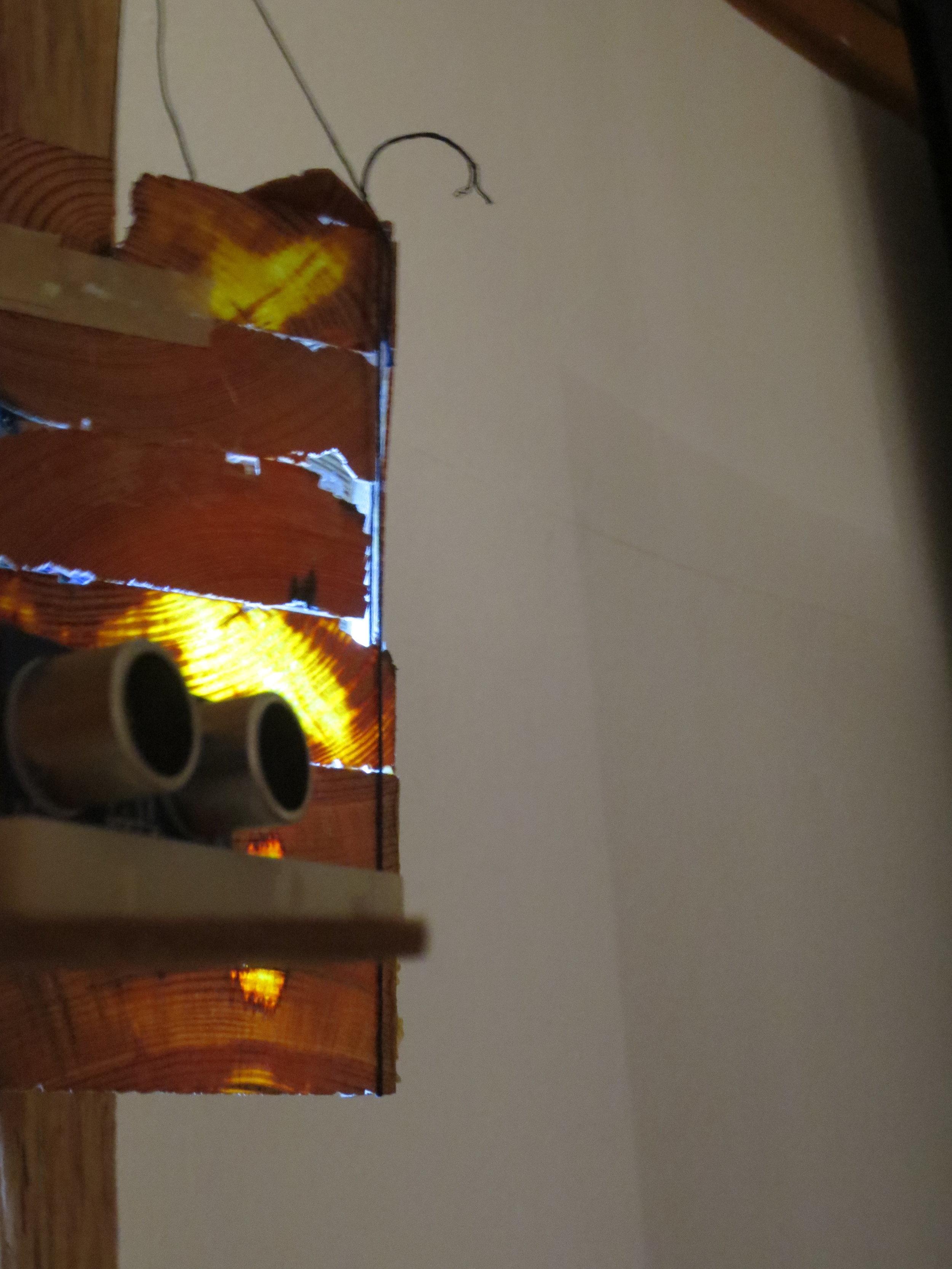 Arduino-controlled sonic sensor that controls light behind wooden lantern.