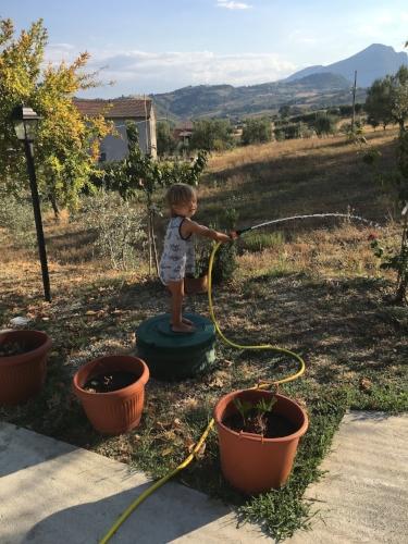 Nico watering Nona's plants in her garden in Abruzzo.