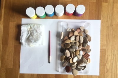 Story Stone Dominoes with basic supplies: paint, brush, and a surface to paint on.