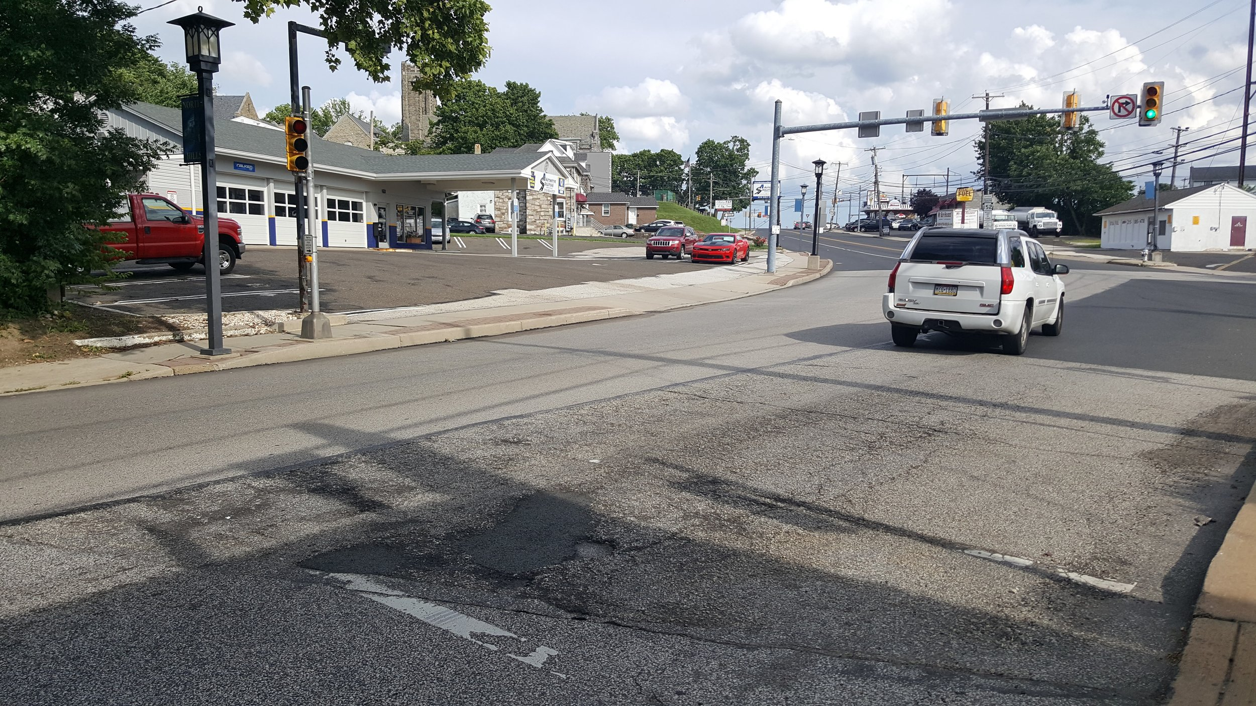 Intersection of Limekiln Pike and Mt Carmel Ave. Pedestrian signal, but no crosswalk.