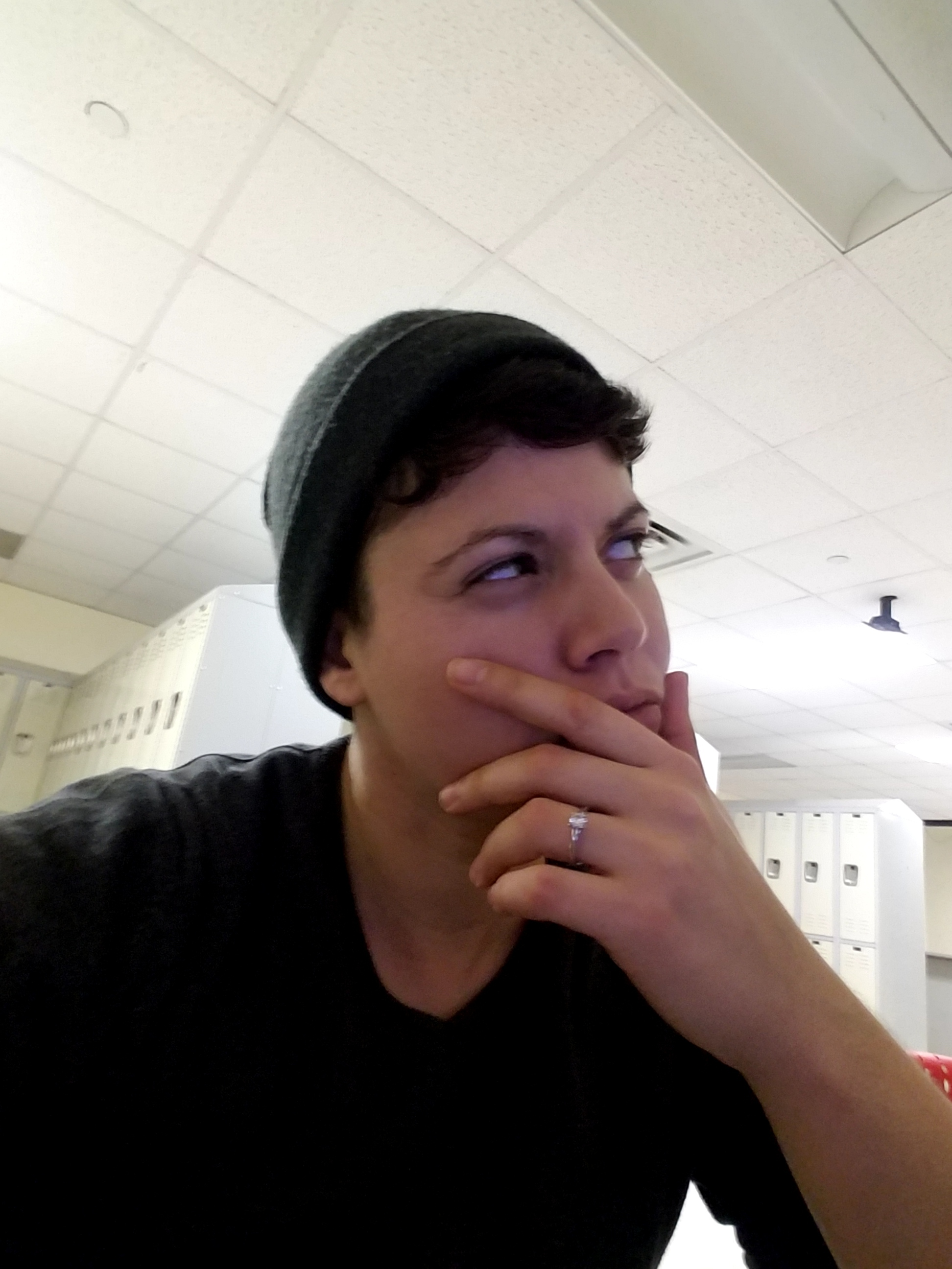 A white enby with short, dark brown hair (me!!) strokes their chin, looking up and away in concentration. They are wearing a grey-green beanie and a grey sweater.