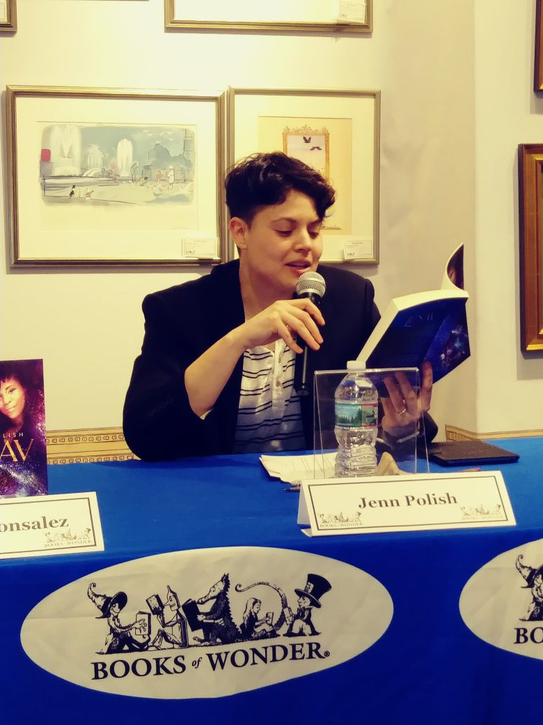 A photo of a white person with short dark hair sitting at a table at Books of Wonder, a microphone in their hand, reading a passage from their debut novel, LUNAV.