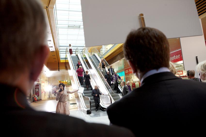 Marion Hackl (Regisseurin/Moderatorin) mit Chor auf der Rolltreppe © Magdalena Lepka