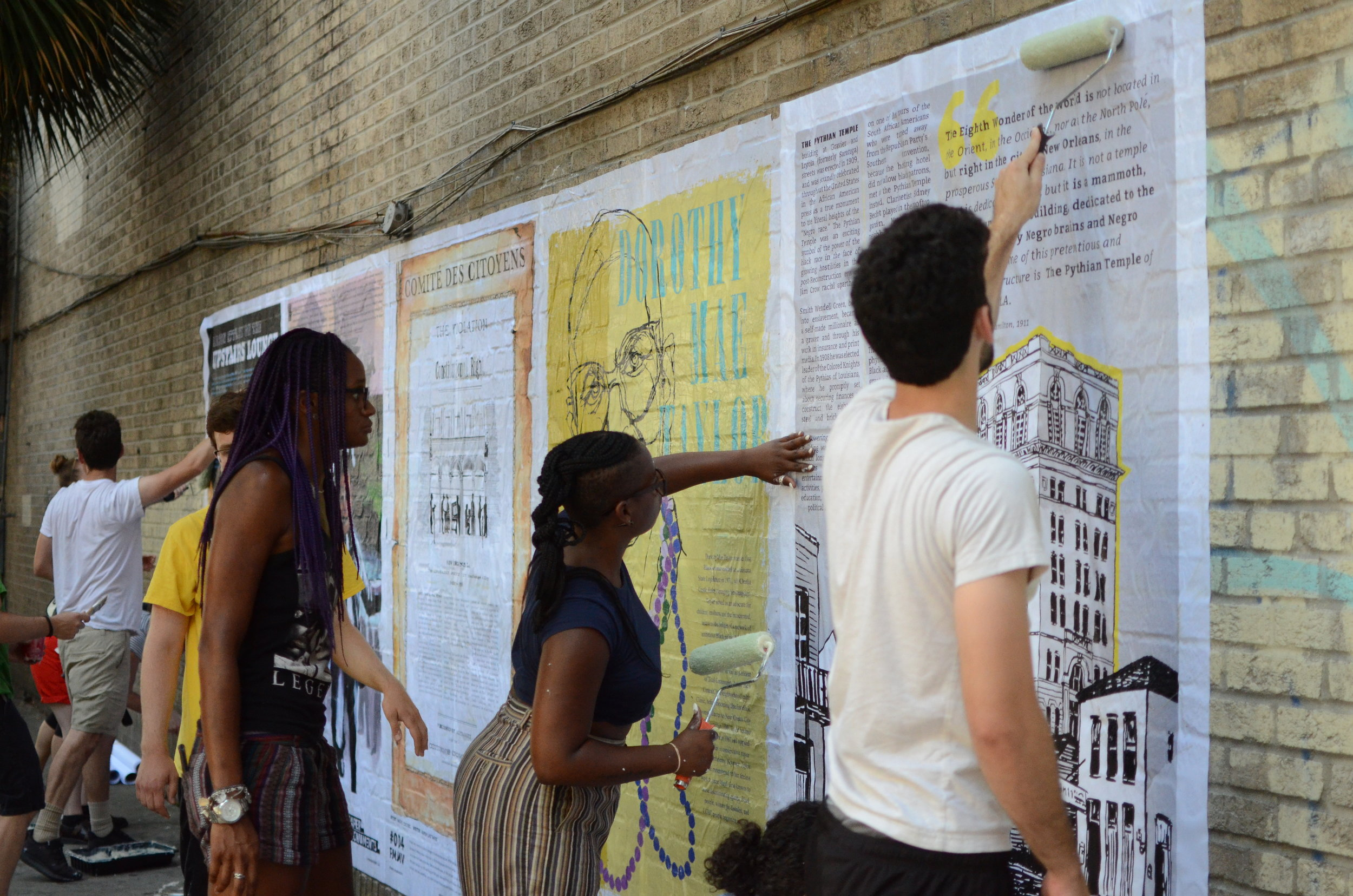 Volunteers work to smooth out wheatpaste bumps as Outreach Coordinator, Brit Lindsey, looks on. (Photo Credit: Chris Daemmrich)