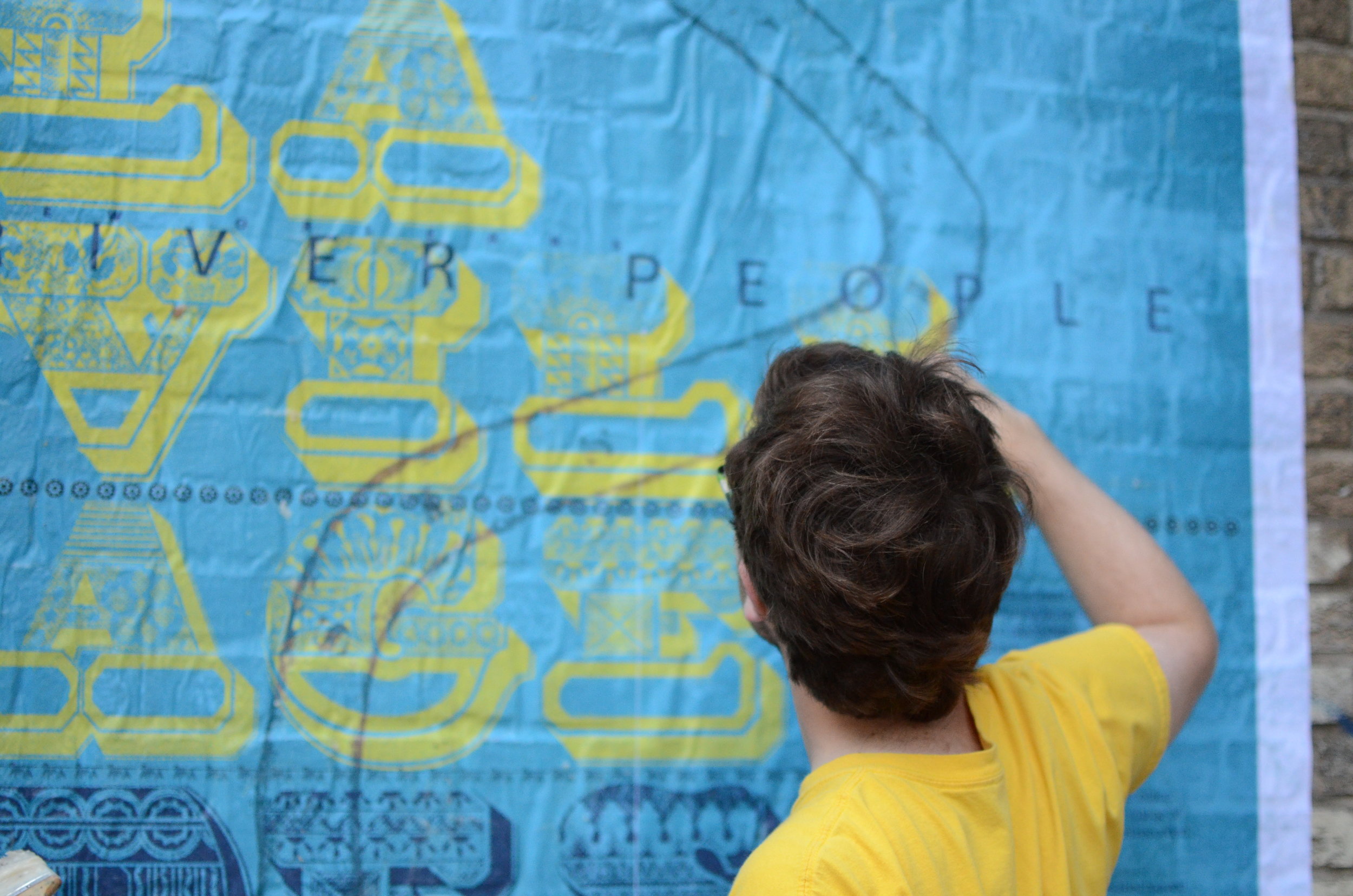 A volunteer in the process of putting up a poster commemorating La Villa De Chapitoulas. Daniela Marx created the artwork, and Shannon Lee Dawdy wrote the narrative for the poster. (Photo Credit: Chris Daemmrich)