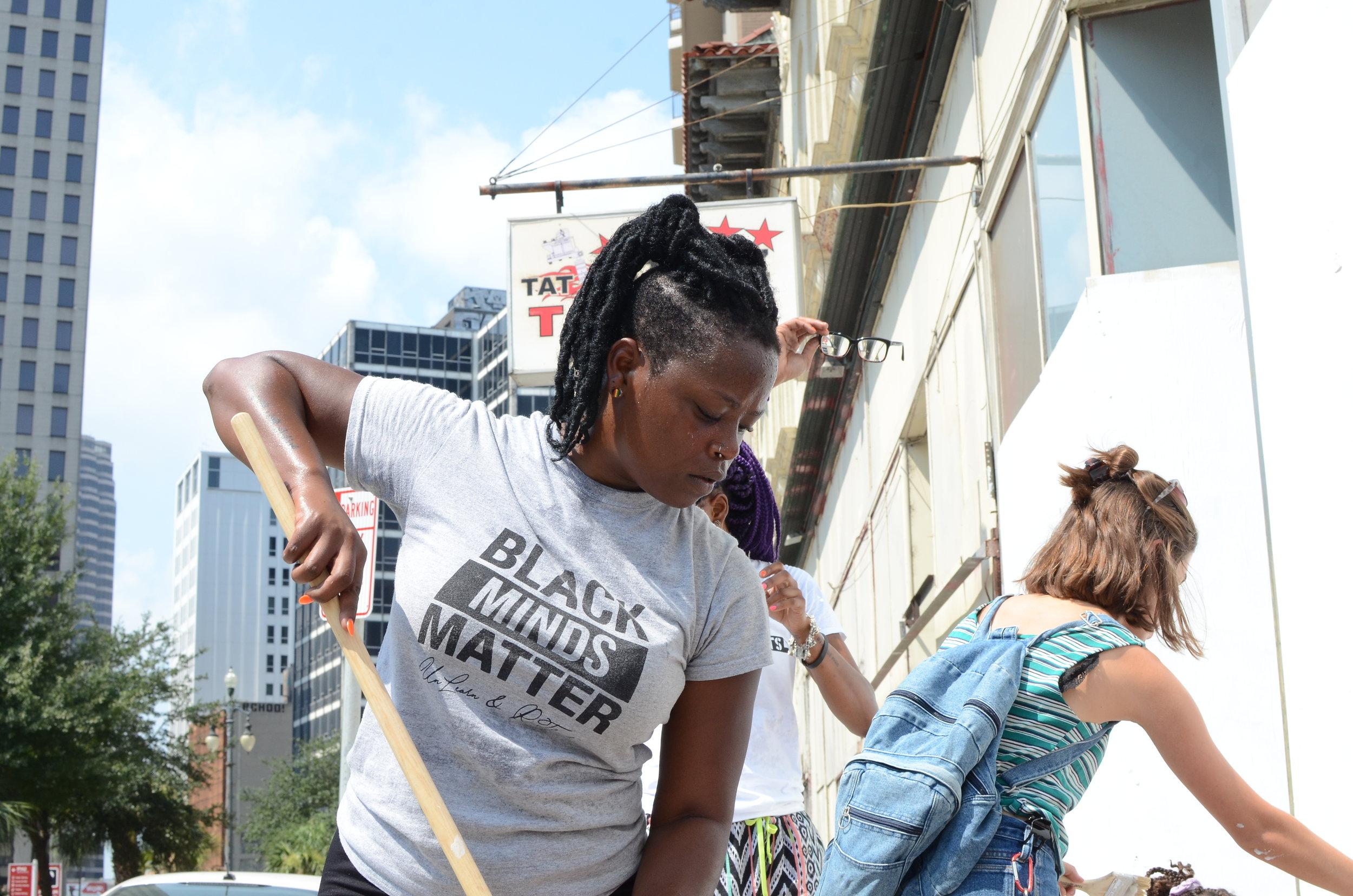 Paper Monuments volunteer Kodi prepares to paste at the Rampart Street site.