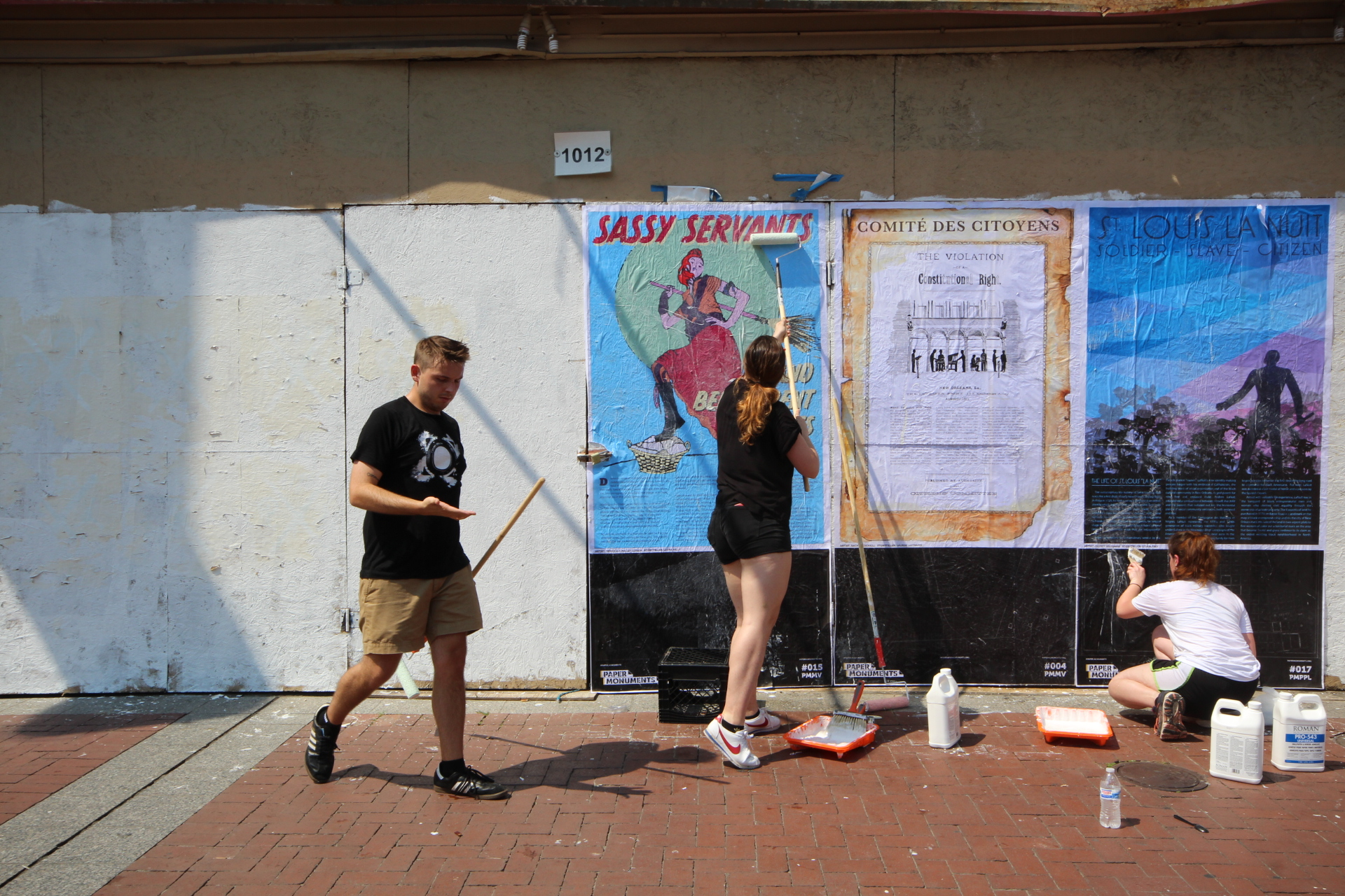 Paper Monuments volunteers Corbin and Maggie and team member Isa Siegel install poster panels at the Canal Street site.