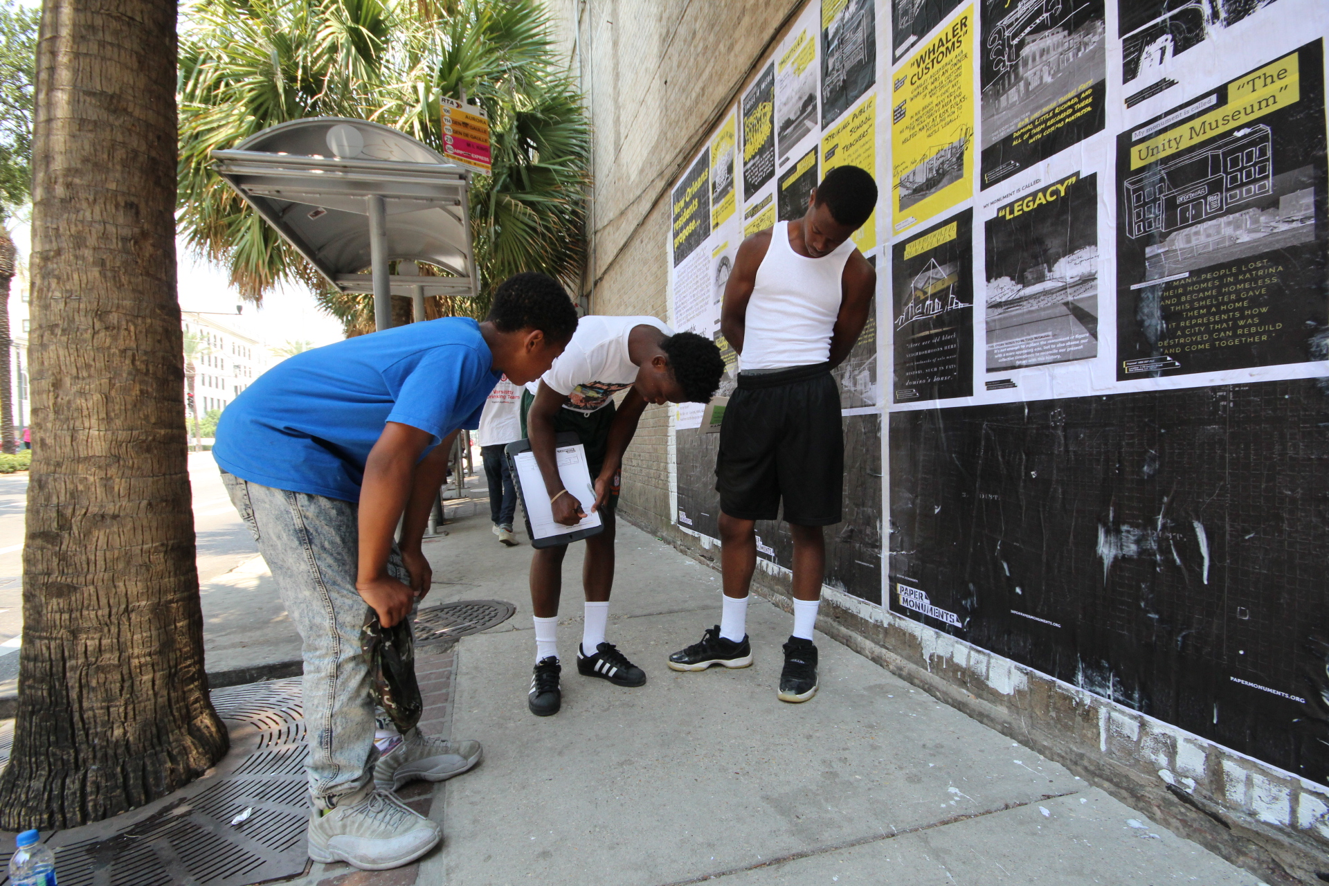 High-school students passing through the bus stop fill out a Public Proposal at the Elk Place site.