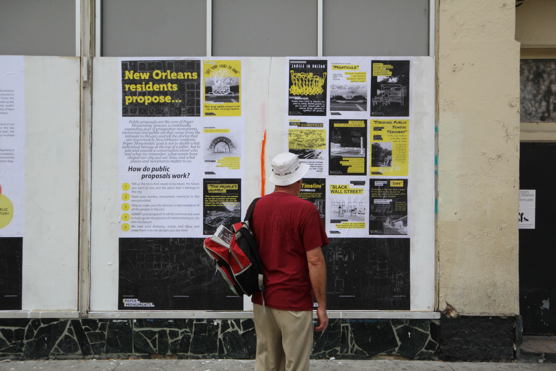 A passer-by reads Public Proposal panels at the Rampart Street site.