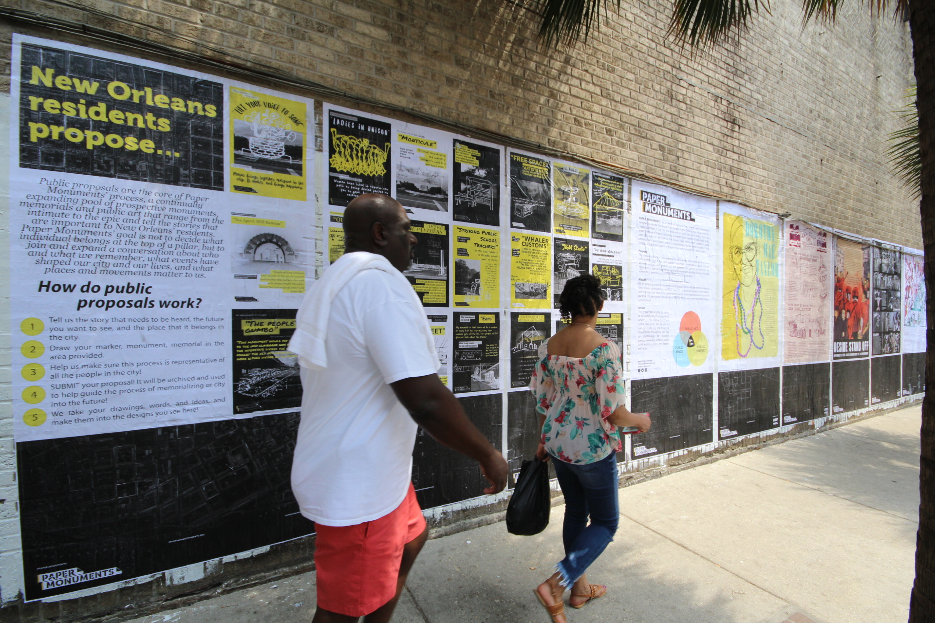 Passers-by read Public Proposal panels at the Elk Place site.