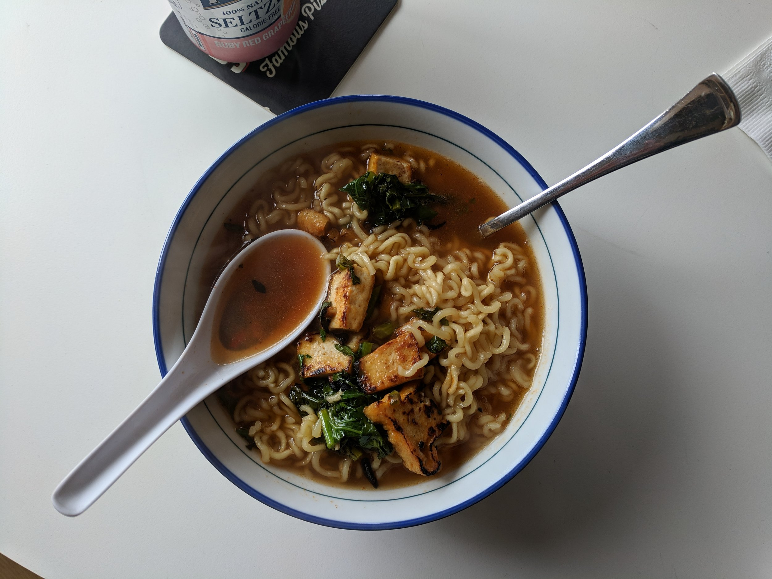 "Did I almost forget lunch again?! Here's a quick lunch of nong shim ""mild"", greens & fried tofu + hot sauce and obligate seltzer can"