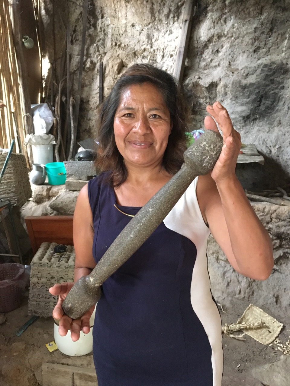 """Vicky holding her great-grandmother's """"mano""""—grinding tool that accompanies the metate."""