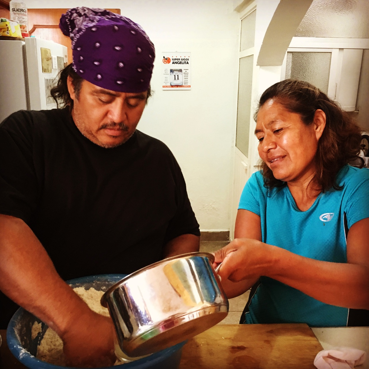 Vicky teaching Noel just how to mix the masa.