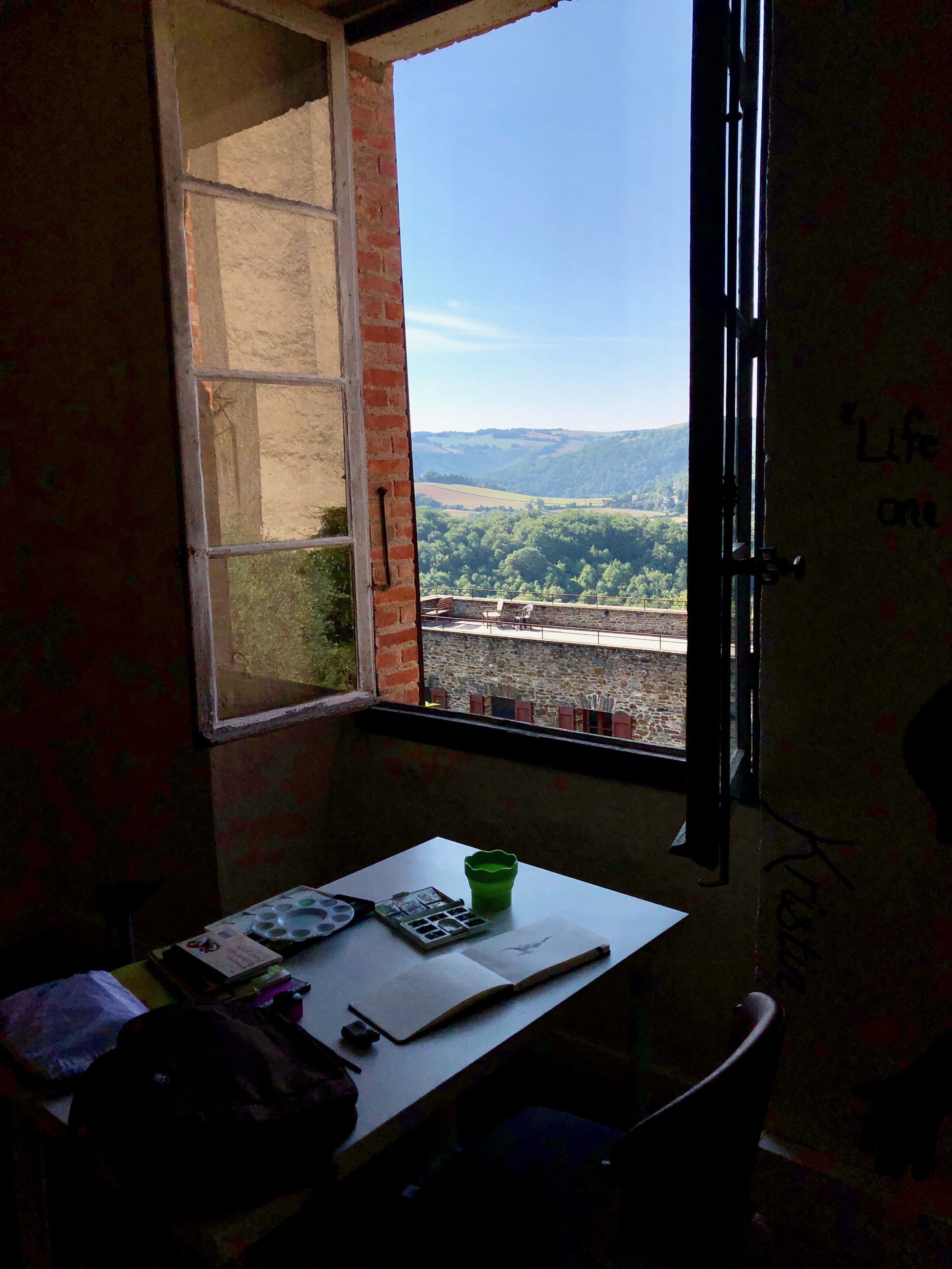 A workspace with a view set up in common room of Le Prieuré