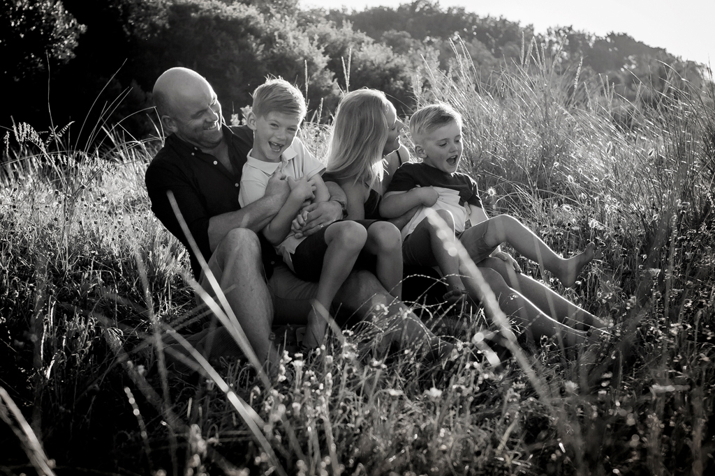 Family cuddling in golden light on rosebud beach