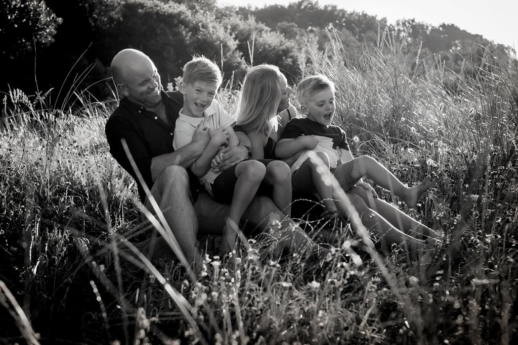 Family cuddling in golden light on rosebud beach