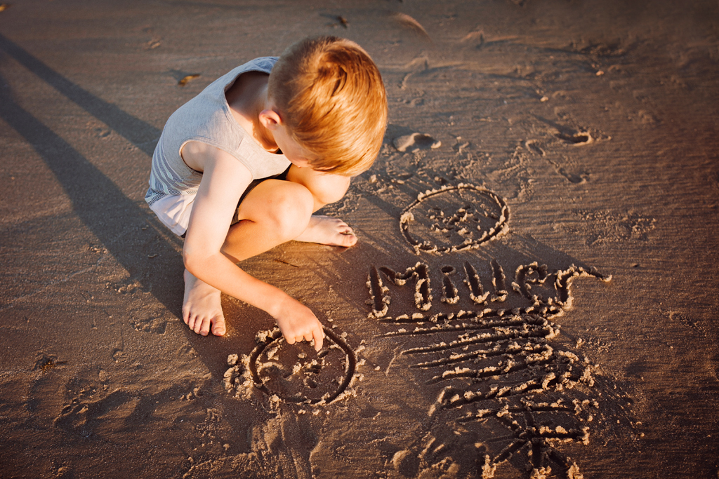 Candid family portrait - writing his name in the sand