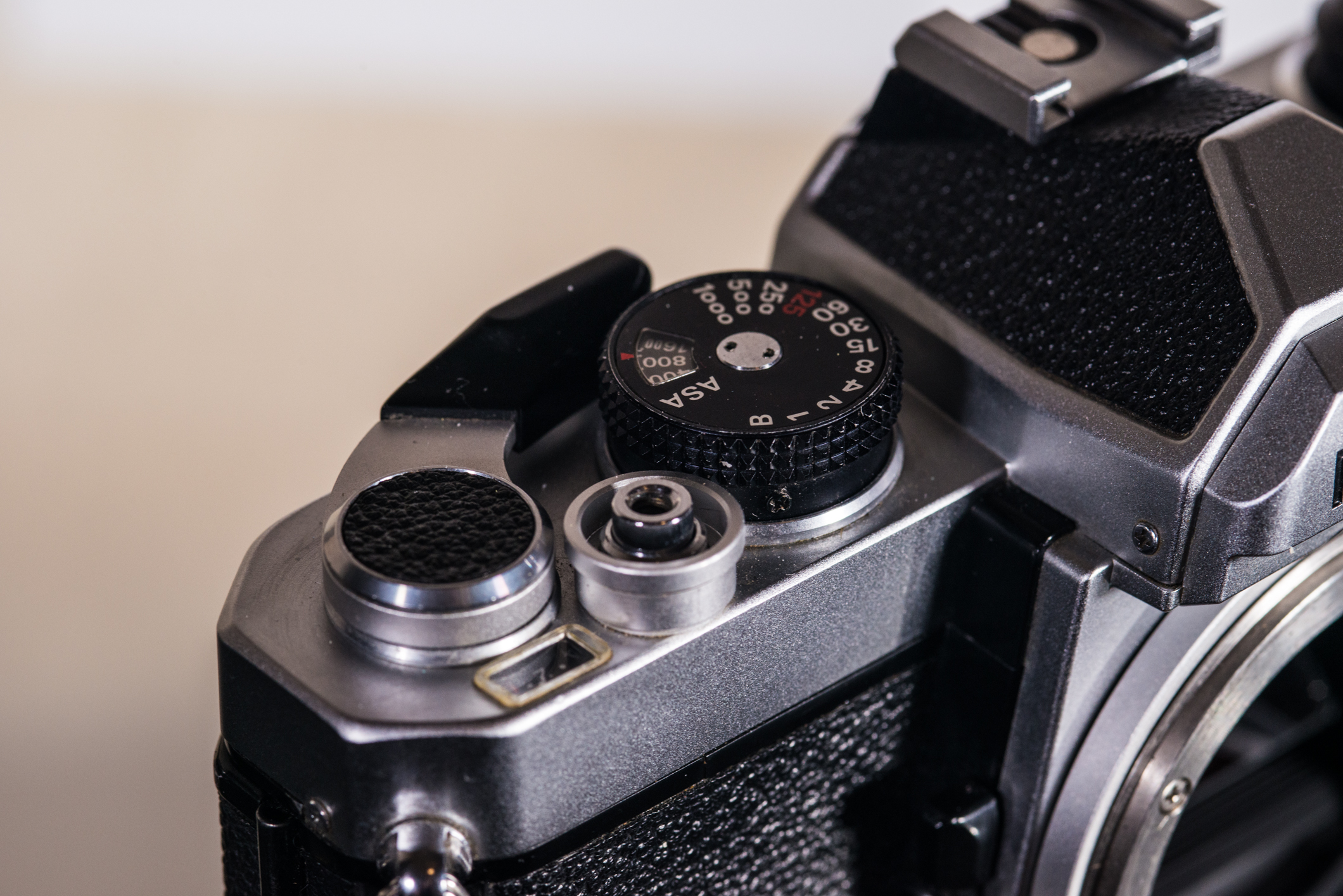 The FM's main controls. Flash X-sync, marked in red, is limited to 1/125. The film advance stopper is hidden behind the shutter speed dial.