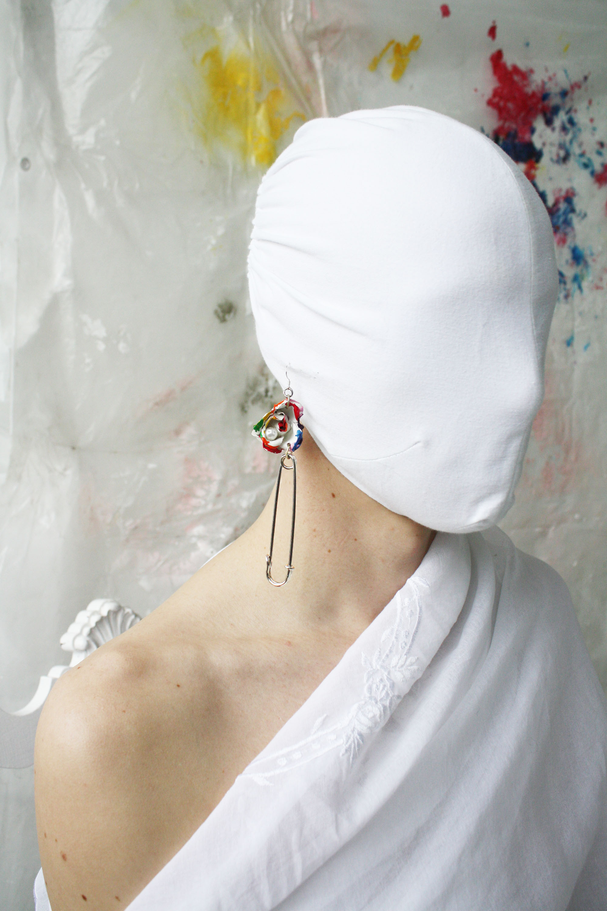 Masked model wearing assemblage earring made of a kilt pin, painted rose and pearl.