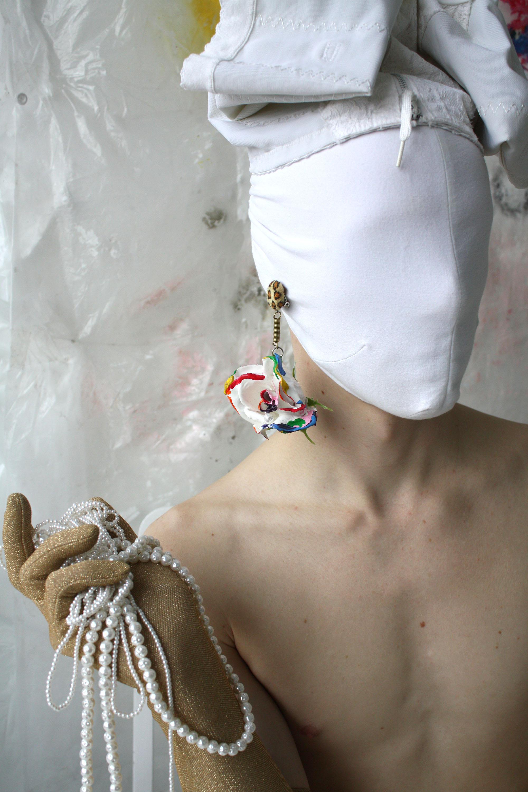 Masked model wearing assemblage earring of painted rose and mixed materials.
