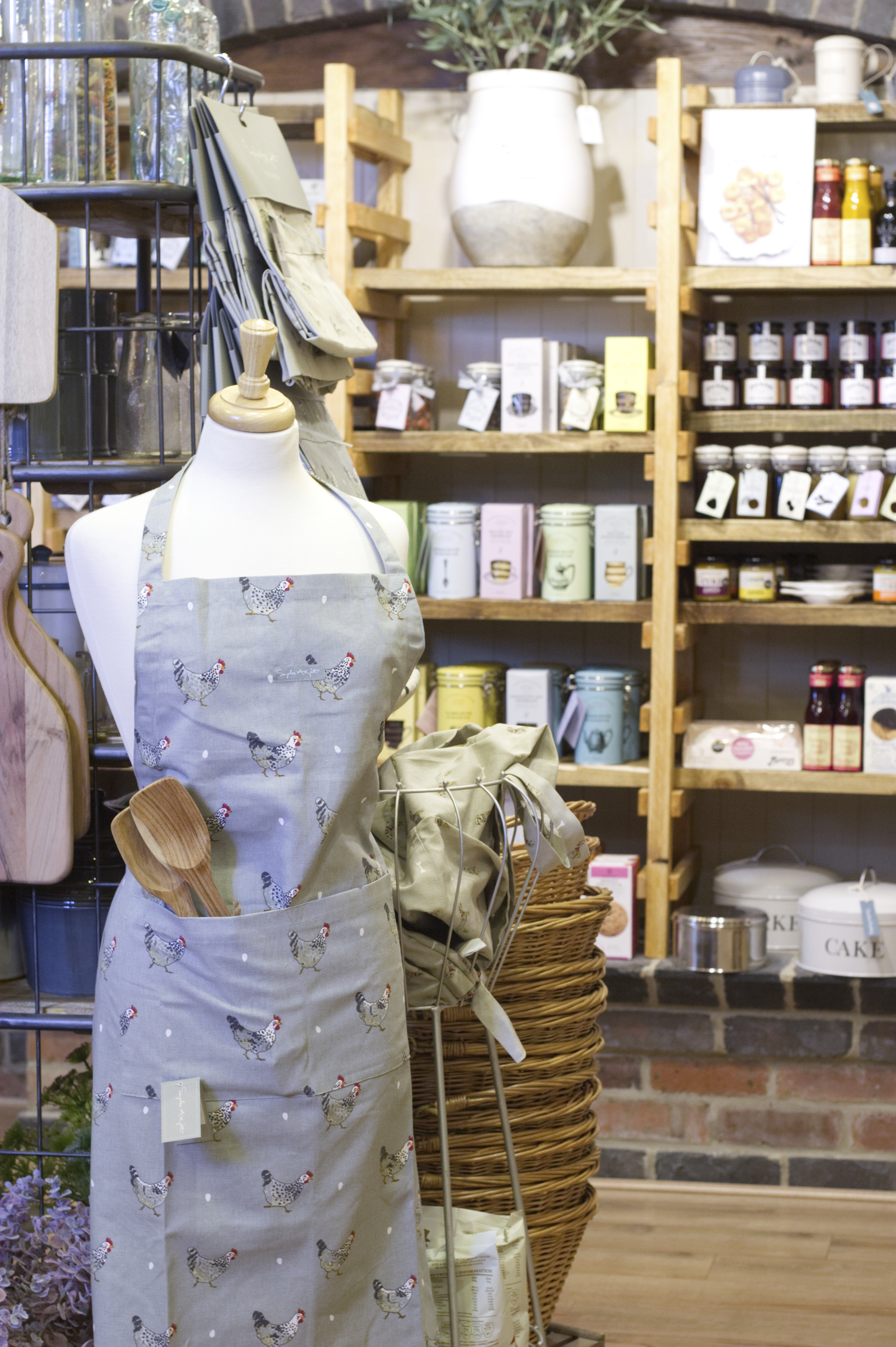 Shop manikin wearing an apron standing in front of shelves of products