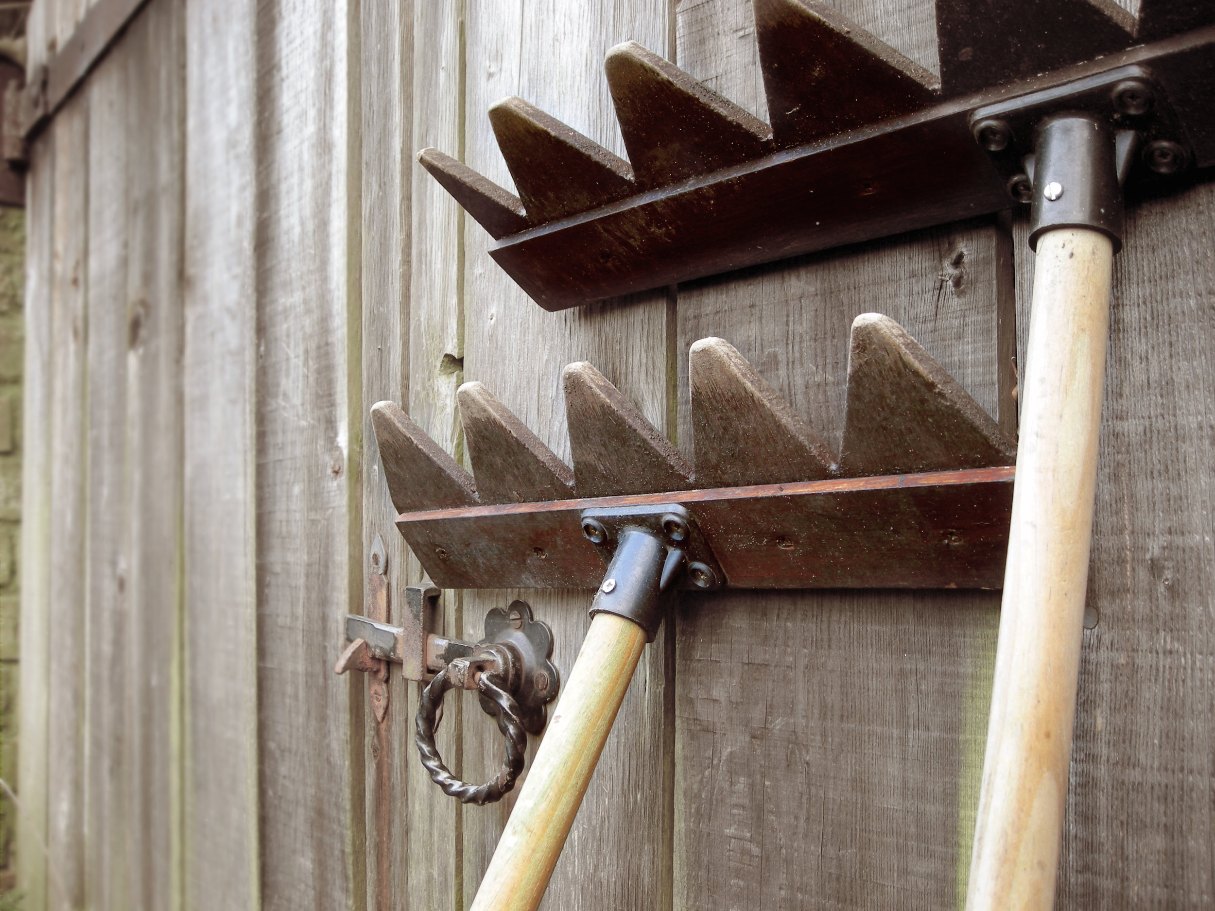 Two gravel rakes leaning against wooden gate