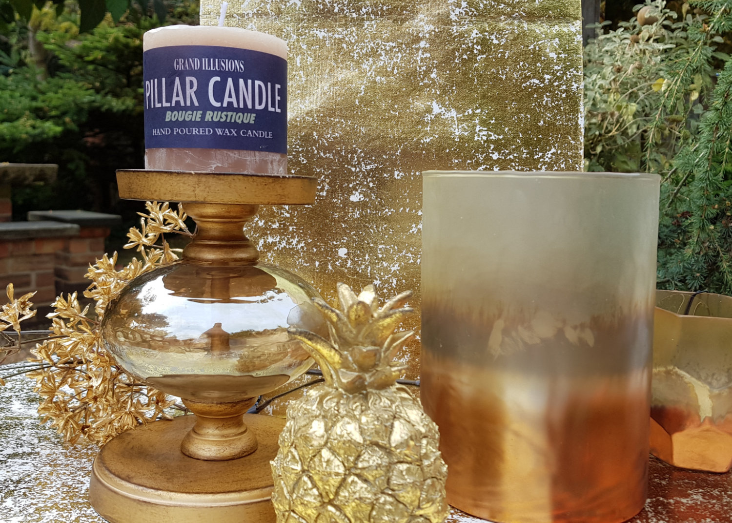 Chunky, gold candlestick, gold coloured decorative pineapple and golden glass tea-light holders.