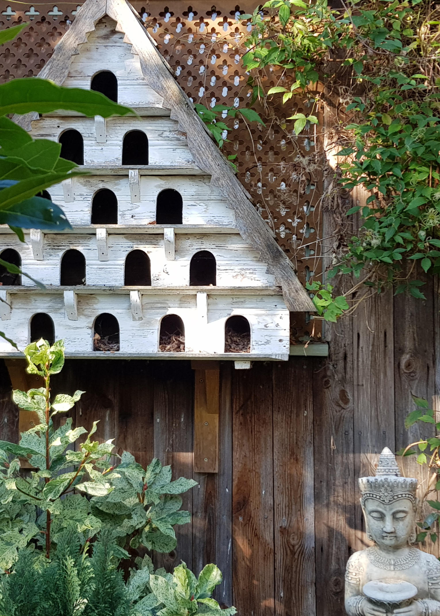 Triangular, white painted bird house with five floors.