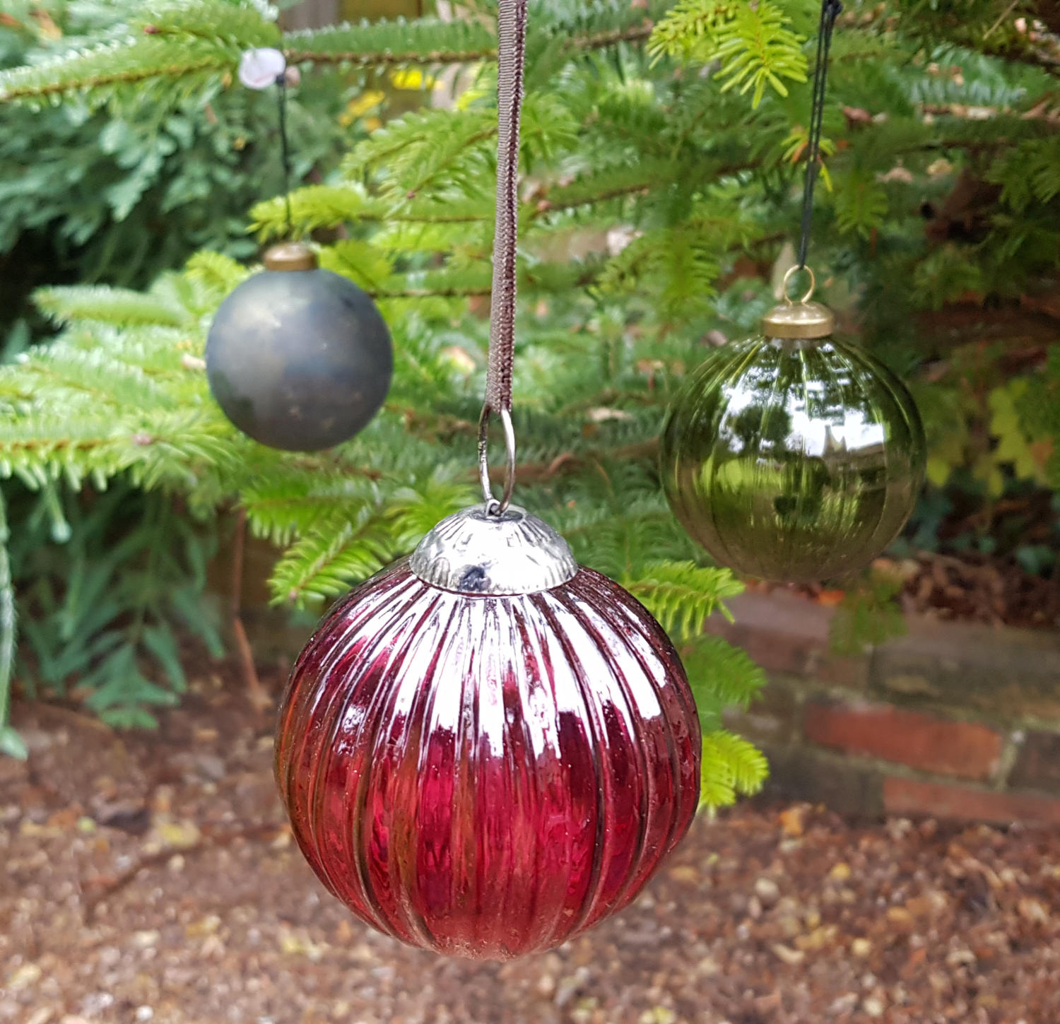 Vintage-style glass baubles on a Christmas tree in the garden at the Bottle Kiln.