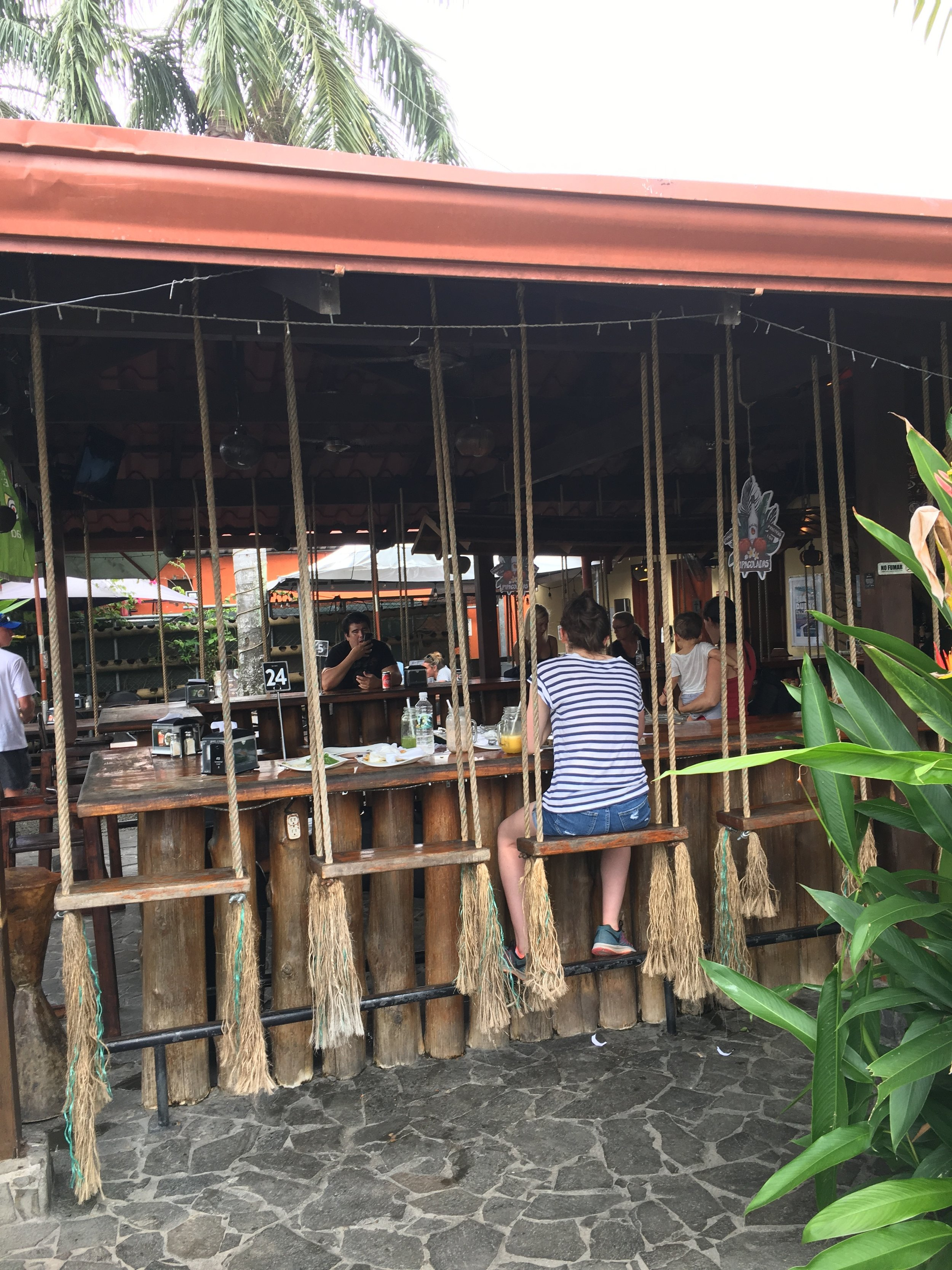 Taco Bar in Jaco: Haleigh on the swing seats