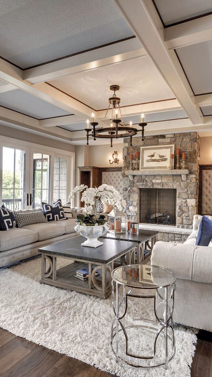 The wood paneled ceiling, chrome accent furniture, furry rug and stone fireplace stand out against the otherwise neutral palette.    Courtesy of Pinterest
